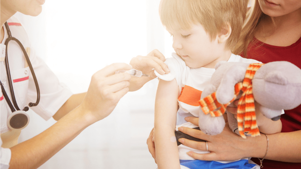 Young child getting a vaccination from a doctor