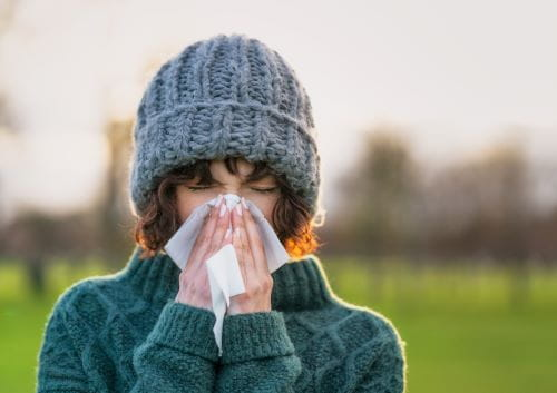 Young woman sneezing from flu symptoms