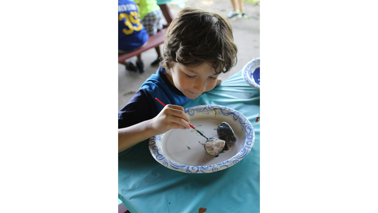 young boy painting a rock at CompassionNet's SibsROCK! day