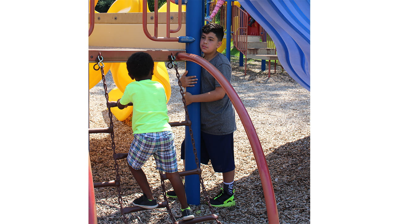 young boy playing in a playground at CompassionNet's SibsROCK!