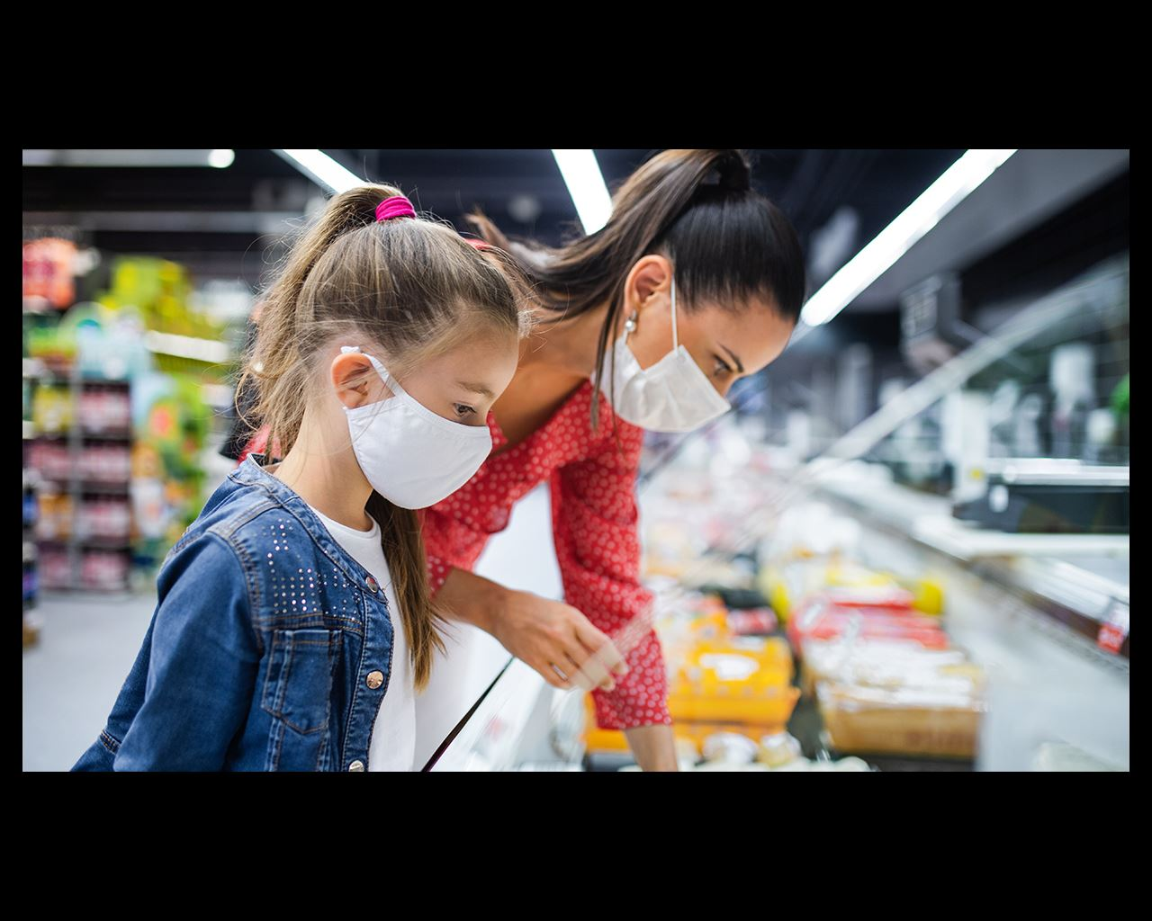 mother and daughter masked at a grocery store