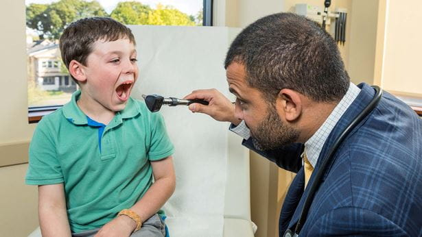 Dr. S. Shahzad Mustafa checking a patient's tonsils