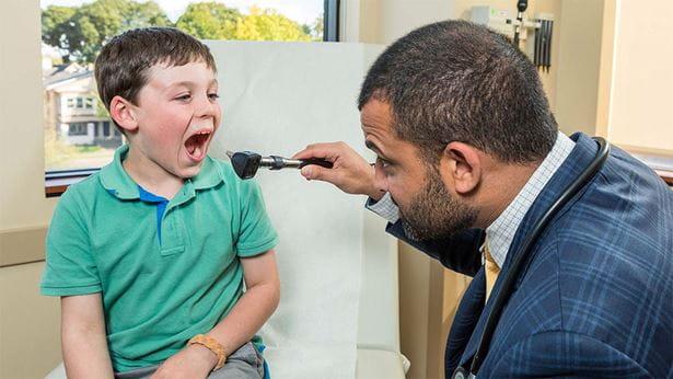 Dr. Mustafa looks down his patient's throat