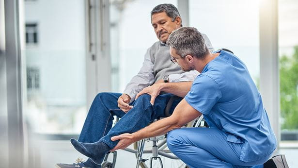 A man on a wheelchair having muscle tightness challenges and being examined by a healthcare provider