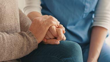 Elderly woman holding a family member's hand
