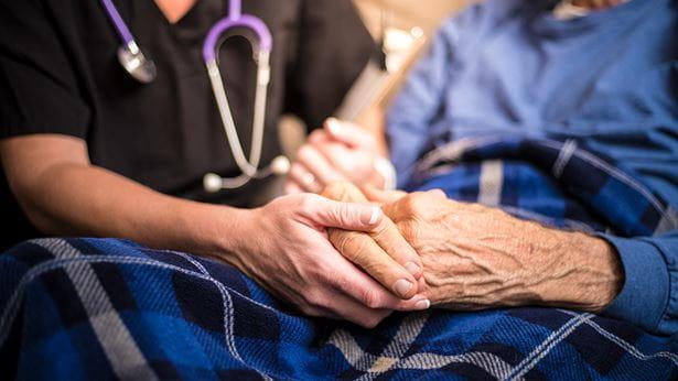 Nurse holding a senior's hand in a nursing home