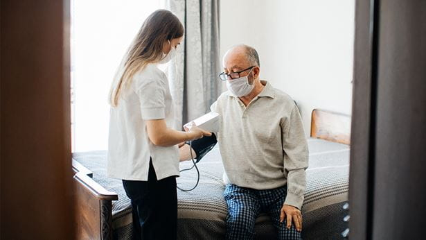 Young healthcare worker measuring blood pressure of a senior man