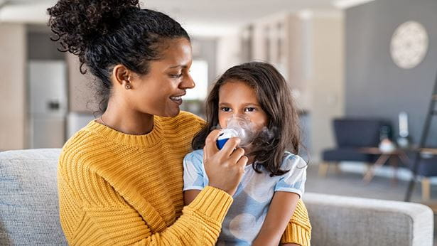 image of a mother helping her daughter use her asthma inhaler