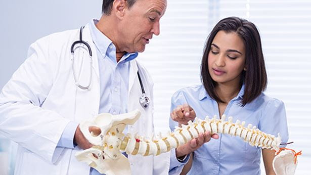 doctor and patient looking at a spine diagram