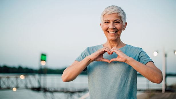 Women with white hair and blue t-shirt holding her hands in the shape of a heart